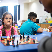 Catherine Denetclaw, 9, watches Isaiah McSweeney, 17, as she waits for her turn in their chess match Wednesday, May 22 during Chess Club at the Octavia Fellin Public Library Children's Branch.