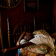 """Korwin """"Quan"""" Wilson, 17, stretches as he awakes in his aunt Ellen """"El"""" Wilson's bed in the Baptist Town neighborhood of Greenwood, Mississippi on Saturday, February 19, 2011. The night before she had to be taken to the hospital for medical complications and after returning to her house, Korwin fell asleep in her bed, his aunt on the sofa."""