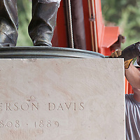 Patrick Sheehy, with Vault Fine Art Services cuts through the anchor rods in the base of the Jefferson Davis Statue, before the statue was lifted and loaded on to a flat bed truck. The Davis statue and the Woodrow Wilson Statue will be taken to the Briscoe Center for American History where they will be refurbished. Sunday Aug. 30, 2015