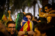 A young couple wrapped in a Catalonian flag is seen reacting after leader of Catalonia, Carles Puigdemont has declared the region has earned the right to become a nation.