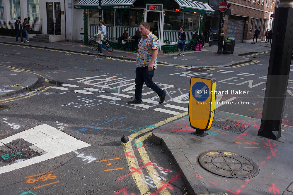 A pigeon and a man in a stylish shirt walk over road junction construction markings in Soho, central London.