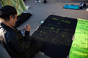 In between performers outside the National Gallery a man paints a visual description of ISIS' view of women, - 2 women equal 1 man.