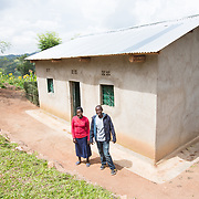 CAPTION: Jean Claude and Claudine stand proudly in front of the home that is now theirs. Jean Claude has consistently set aside a portion of his earnings to ensure good quality housing. The siblings have been living in their own accommodation since the end of 2013. The cost of building the home was FRW 200,000, and it was through saving hard that Jean Claude was able to pay the bulk of this sum, though he also topped up the money he'd saved with consumption support received from Concern Worldwide. LOCATION: Kabuga Village, Gafumba Cell, Rusatira Sector, Huye District, South Province, Rwanda. INDIVIDUAL(S) PHOTOGRAPHED: Claudine Iradukunda (left) and Jean Claude Minani (right).
