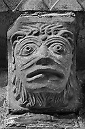The Stone Bestiary - Black and white photo art print of Norman Romanesque exterior corbel no 38 - sculpture of a head, half man half lion with a mouth like a theatrical mask. The Norman Romanesque Church of St Mary and St David, Kilpeck Herefordshire, England. Built around 1140 .<br /> <br /> Visit our LANDSCAPE PHOTO ART PRINT COLLECTIONS for more wall art photos to browse https://funkystock.photoshelter.com/gallery-collection/Places-Landscape-Photo-art-Prints-by-Photographer-Paul-Williams/C00001WetsxVxNTo