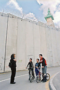 Children on bicycles near the separation barrier, Jerusalem. A mosque appears in the background. Magazine photography by Debbie Zimelman, Modiin, Israel