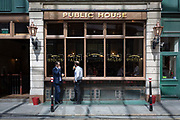 Two afternoon drinkers stand outside a public house pub enjoying cool beers on a hot day in the Square Mile, the capitals ancient financial district dating back to the 1st century Roman era, on 17th Juy 2017, in the City of London, England.