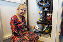 Artist Michelle Baharier, 55, shows how the huge boiler and what she thinks might be a loose, unfitted thermostat switch, for which, despite the nearly £25,000 price tag, she was never supplied any instructions. She is fighting  Southwark Council the freeholders of her 2 bedroom Camberwell flat, which she purchased in 2008 under the Right to Buy Scheme, being forced to pay for the boiler. London, November 16 2018.