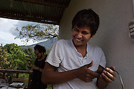 Antonio Cruz Sanchez, 26, selects music to play for his co-worker and roommate Abigail Quic's Birthday. Antonio is always ready with a smile, and a helping hand at the SERES Embassy. San Juan Del Obispo, Guatemala, July 24, 2014