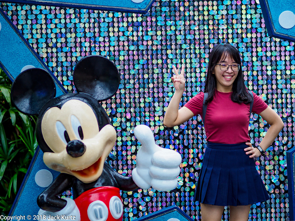 """12 DECEMBER 2018 - SINGAPORE:  A woman poses for a picture with Minnie Mouse at a Christmas display on Orchard Road. Orchard Road is the main shopping district of Singapore and for years hosts a large light display around Christmas. The main sponsor of this year's display is the Disney Company and the displays are decorated with characters from the Disney entertainment universe. This has upset some religious leaders in Singapore and the National Council of Churches of Singapore (NCCS) sent a letter to the Singapore Tourism Board (STB) expressing its concern about the """"increasing secularisation and commercialization of Christmas"""" in Singapore. The STB reached out to the NCCS, but the Orchard Road lights will remain on through the holidays.   PHOTO BY JACK KURTZ"""