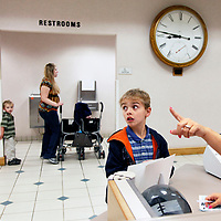 A receptionist at Hardin Memorial Hospital directs Matthew Mason, 9, towards the waiting room.  Matthew has an undiagnosed illness with multiple symptoms. Matthew's mother, Sarah, wants him to learn how to handle this medical treatments independently because he will most likely have medical problems the rest of his life.