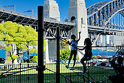 Two children playing on Milsons Point, with Sydney Harbour Bridge in background. Sydney, Australia