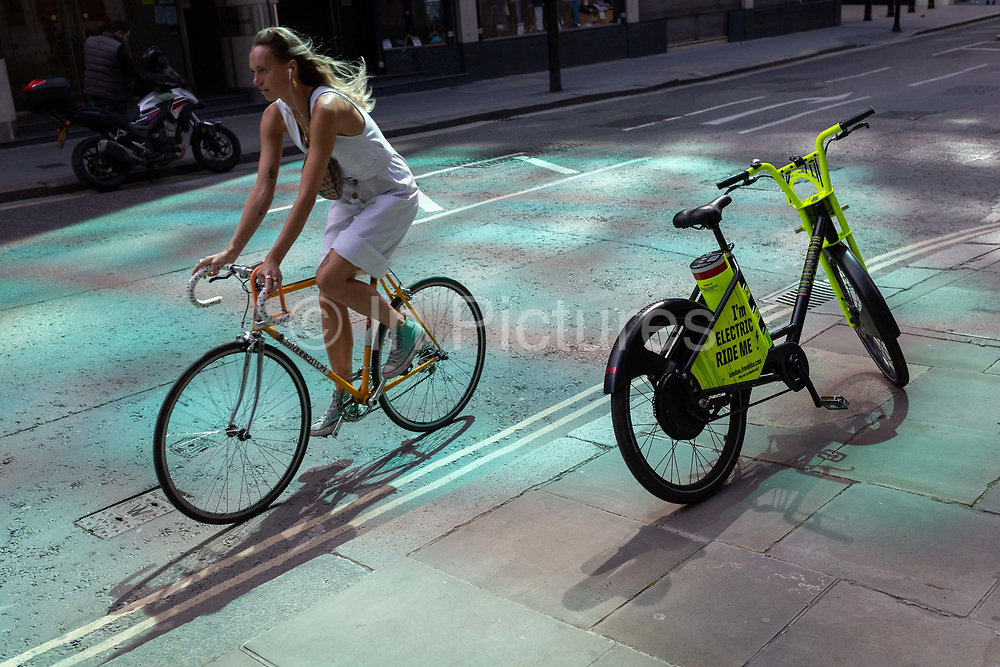 A lady cyclist on her own bicycle pedals past an electric rental Freebike standing on the pavement in reflected light, in the City of London, the capitals financial district, on 20th July 2020, in London, England.