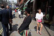 Summertime in London, England, UK. Asian woman in hot pants walks through the West End near to Chinatown.