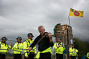 Anti-fracking  activists and protesters outside the gates of Quadrillas fracking site June 31st, Lancashire, United Kingdom. A man plays violin outside the police cordon. The struggle against fracking in Lancashire has been going on for years. The fracking company Quadrilla is finally ready to bring in a drill tower to start drilling and anti-frackinhg activists are waiting in front of the gates to block the equipment getting in. Fracking is a destructive and potential dangerous and highly contentious method of extracting gas and this site will be the first of many in the United Kingdom reaching miles out under ground.