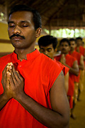 Masseurs at Kalari Kovalikom, begin the day with a session of Kalari Payattu, a martial art discipline which is as much about physical as well as mental strength. Praying is about focusing the mind on the task ahead, Kollengode, Kerala, India