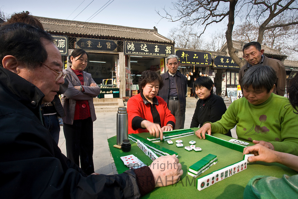 People gather to play Mahjong in the park by the City Wall, Xian, China