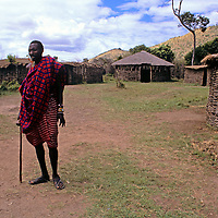 Africa, Kenya, Maasai Mara. A tall Maasai elder stands at the entrance to the boma at Olanana in the Maasai Mara.