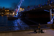A busker plays acoustic guitar with a background of Hungerford Bridge and Charing Cross Station on the opposite bank of the River Thames, on 21st March 2017, Southbank, in London, England.