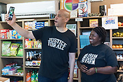 Democratic presidential hopeful Senator Cory Booker, left, talks during a Facebook Live broadcast with Germaine Jenkins, the Chief Farm Officer of the Fresh Future Farm inside the farm store April 27, 2019 in North Charleston, South Carolina. Booker spent his 50th birthday helping out at the urban farm as part of his Justice For All tour.