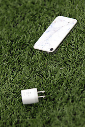 18 October 2014:  iPhone and charger lie on the turf during an NCAA division 3 football game between the Augustana Vikings and the Illinois Wesleyan Titans in Tucci Stadium on Wilder Field, Bloomington IL