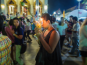 "13 MAY 2013 - BANGKOK, THAILAND:  A woman carries a candle lantern during Vesak services at Wat That Thong in Bangkok. Vesak, called Wisakha Bucha in Thailand, is one of the most important Buddhist holy days celebrated in Thailand. Sometimes called ""Buddha's Birthday"", it actually marks the birth, enlightenment (nirvana), and death (Parinirvana) of Gautama Buddha in the Theravada or southern tradition. It is also celebrated in Cambodia, Laos, Myanmar, Sri Lanka and other countries where Theravada Buddhism is the dominant form of Buddhism.    PHOTO BY JACK KURTZ"