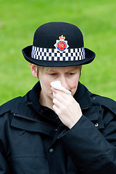 © Licensed to London News Pictures. 04/10/2012. Manchester, UK . A police officer listening to the service outside the cathedral wipes tears from her cheek . 100s of police in Manchester city centre for the funeral of PC Fiona Bone at Manchester Cathedral . Bone was murdered in a gun and grenade attack alongside PC Nicola Hughes when responding to a suspected burglary at a house in Hattersley in Tameside on 18th September . Dale Cregan is currently on remand , accused of the two murders . Photo credit : Joel Goodman/LNP