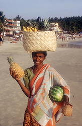 Fruit seller and tourists on the beach at Kovalam beach; Kerala; India,