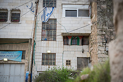 2 March 2020, Hebron: The H2 area of Hebron is under Israeli military control. Palestinians cannot enter into the area unless they have residence there, and even then, cannot drive a Palestinian car inside the area. Here, the home of a Palestinian family who have seen two of their floors confiscated by Israeli settlers, who now live on top of them.