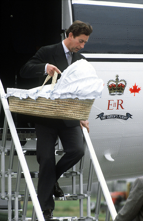 Prince Charles,Prince of Wales carries his new-born son Prince William in a moses basket down the steps of the Queen's flight on arrival in Aberdeen, Scotland,UK in September 1982. Photographed by Jayne Fincher