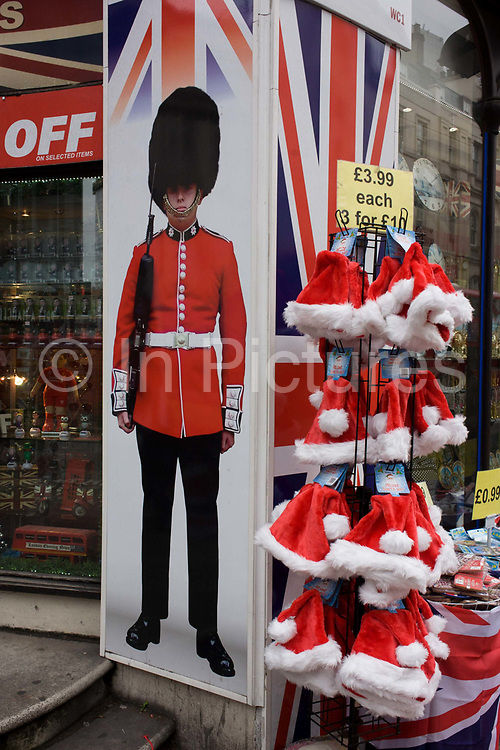 Tacky Christmas tourist trinkets with santa hat and grenadier soldier on sale outside a discount shop in New Oxford Street in central London. There are discounts to be had, deals for passers-by to be enticed by as they walk through this area of the capital: Xmas Santa hats selling for £3.99 each or 3 for £10 - a multibuy for the Christmas season. Central to this scene is a guardsman in red tunic and carrying his weapon, as seen on countless ceremonial events such as Trooping of the Colour parade each summer.