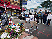 """12 JUNE 2020 - MINNEAPOLIS, MINNESOTA: A man takes pictures with his cell phone at the impromptu memorial for George Floyd at the corner of 38th Street and Chicago Ave. in Minneapolis. The intersection is informally known as """"George Floyd Square"""" and is considered a """"police free zone."""" There are memorials to honor Black people killed by police and people providing free food at the intersection. Floyd, an unarmed Black man, was killed by Minneapolis police on May 25 when an officer kneeled on his neck for 8 minutes and 46 seconds. Floyd's death sparked weeks of ongoing protests and uprisings against police violence around the world.          PHOTO BY JACK KURTZ"""