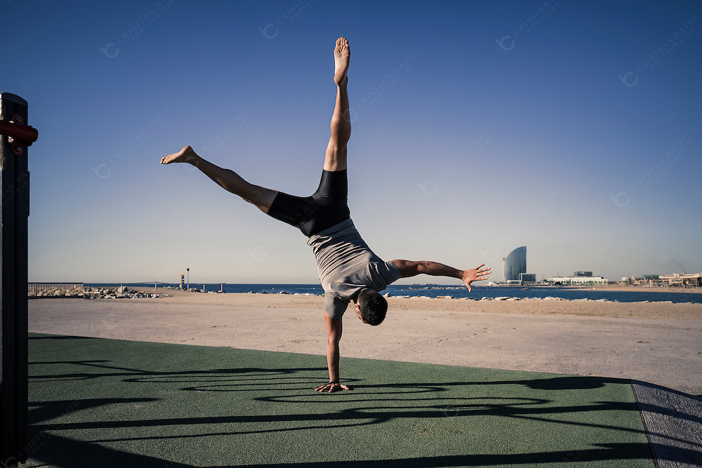 Young man doing a headstand as part of his calisthenics workout routine