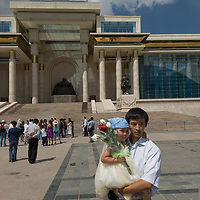 A father and his daughter stand outside the Mongolian Parliament building - dominated by a sculpture of Genghis Khan - in Sukhbaatar Square in downtown Ulaanbaatar.