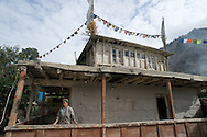 A woman stands on the porch of her home in the village of Giabong in the Ropa Valley, Himachal Pradesh, India