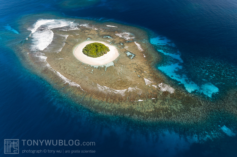 This is an aerial view of Lua Loli island in the Vava'u island group of the Kingdom of Tonga. From this perspective the extensive reef structure surrounding the visible portion of the island is apparent.