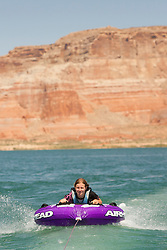 North America, Arizona, Page,  Lake Powell.  Girl (age 10) tubing behind motorboat.  MR