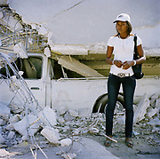 "Nadine Pleato, opposite a collapsed building in down-town Port Au Prince . She is living in a garage at Latimer 54, near Paloma. She says: ""I have just purchased this bag so I can pack a few things and leave Port Au Prince for the provinces. My house was completely destroyed and I lost all my clothes in the quake. All I have left is four pieces of clothing: a skirt and what I am wearing. I have to live and bathe in the street..I didn't know if my mother was alive for six days until she arrived from the provinces with supplies. I was so relieved but I still haven't seen my boyfriend since the morning of the quake. We were with each other a year. He must be dead but I will never know for sure. It's hard to carry on.  How can we be normal now?"""