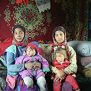 Two Roma Mothers with their children in a gypsy community in Copsa Mica, Transylvania, Romania. 23rd July 2011. Photo Tim Clayton