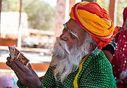 Traditional Rajasthani  musician playing cards on the 20th January 2018  in the village of Shilpgram, Udaipur, India. The individual villages each have their own distinctive turbans both in colours and the methods of tying.