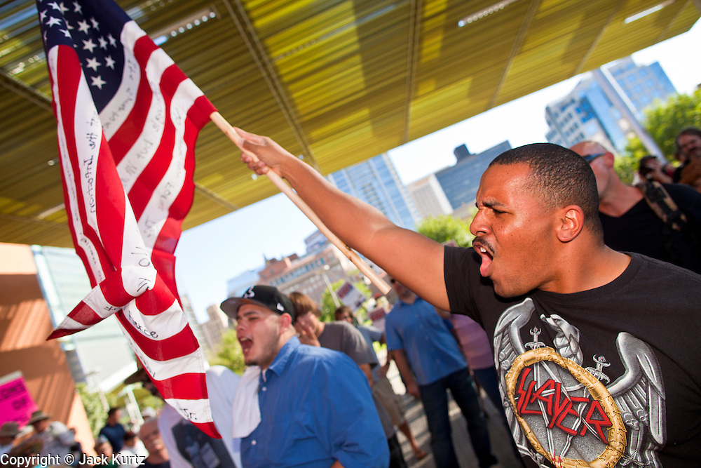14 OCTOBER 2011 - PHOENIX, AZ:   KRISTOPHER MERCHANT waves an American flag before the Occupy Phoenix march Friday. About 300 people participated in the Occupy Phoenix march through downtown Phoenix Friday evening, Oct. 14. The march was the first event in the Occupy Phoenix protests which start with the occupation of Cesar Chavez Plaza, a large square in downtown Phoenix.  PHOTO BY JACK KURTZ