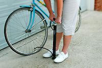 woman pumping up the tire of bicyce in the driveway of a house by the garage door