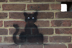 Wokingham, UK. 8th June, 2021. A black cat stencil with stick-on eyes by a street artist dubbed 'Catsy' by appreciative local residents. There are believed to be around 30-40 such black cat stencils sprayed around the town by the anonymous street artist.