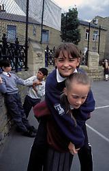 Schoolgirls playing in primary school playground; UK