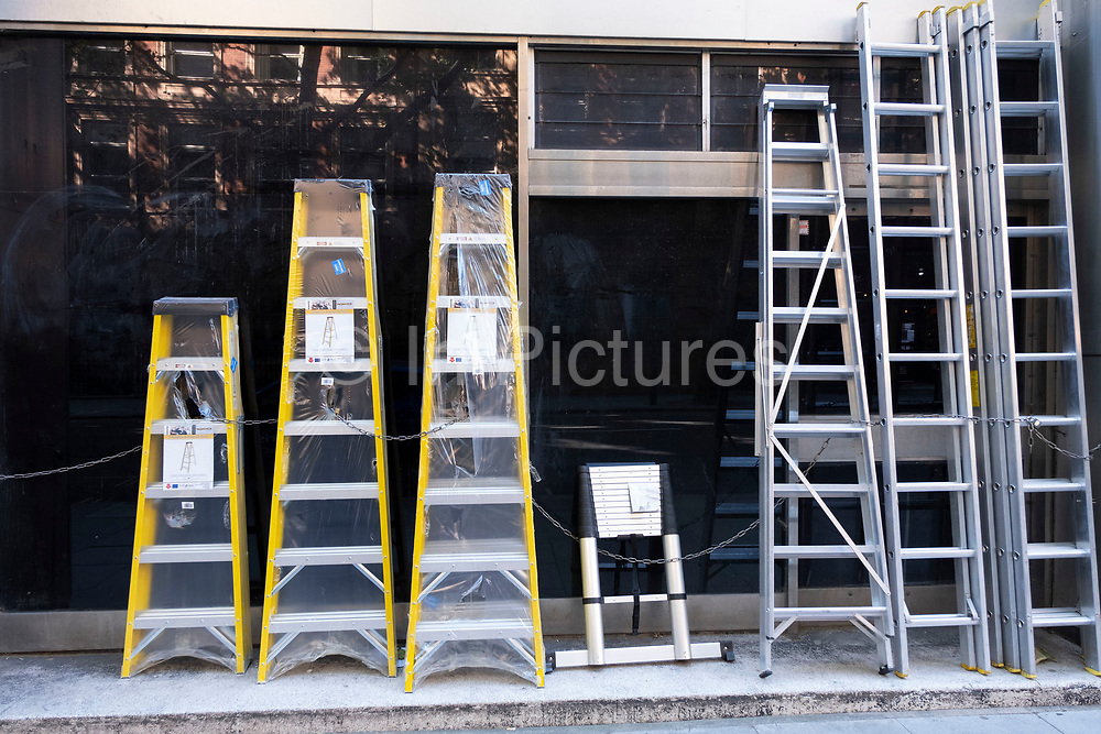 Various heights and sizes of ladder outside a hardware store on 25th June 2020 in London, United Kingdom. Plastic wrapped step ladders and extension ladders are available.