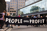 Crowds of climate activists from Extinction Rebellion hold up a banner that reads people over profit in front of office blocks on 27th August, 2021 in London, United Kingdom. The activist group Extinction Rebellion XR are planning actions of disruption for two weeks straight beginning on August 23rd, 2021 in an effort to bring awareness and priority to the global climate emergency in advance of the COP 26 Summit which will be held in Glasgow later this year.
