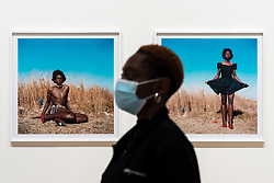 "© Licensed to London News Pictures. 03/11/2020. LONDON, UK. A staff member next to ""Miss D'vine I, Yeoville, Johannesburg"", 2007 by Zanele Muholi. Preview of the first major UK exhibition by South African visual activist Zanele Muholi at Tate Modern.  260 photographs document black lesbian, gay, trans, queer and intersex lives in South Africa.  The show runs 5 November to 7 March 2021, but will be interrupted by England's coronavirus pandemic lockdown currently due to last 5 November to 2 December.   Photo credit: Stephen Chung/LNP"
