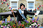The Lord Mayor's Parade, part of the Kilburn Feast on 10th July 2016 in North Yorkshire, United Kingdom. The Lord Mayor, appointed for just one day, tours the village in top hat and sash of office, accompanied by the Lady Mayoress a young man in female clothing and makeup. Proclaiming his authority, he also inflicts small fines on householders and visitors alike for any misdemeanour, real or invented.