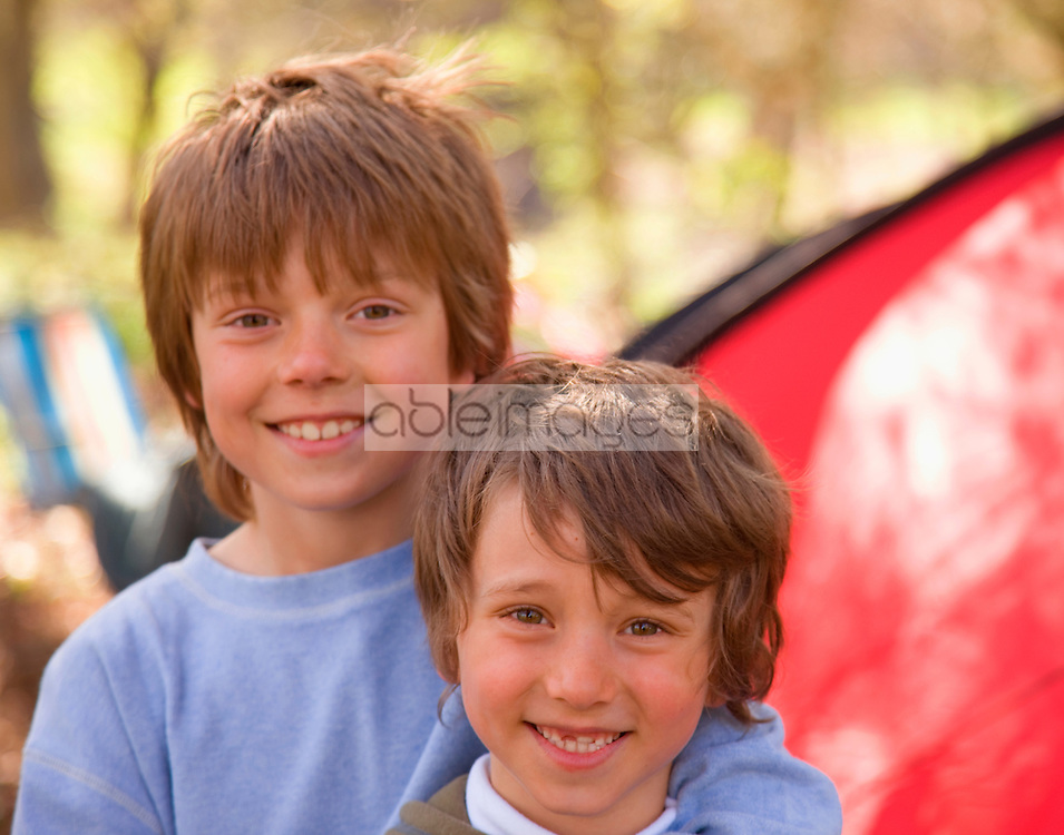 Close up of two boys standing outside tent
