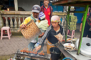 Apr 23 - BALI, INDONESIA -  A Muslim family sells chicken satay (barbecued on a skewer) in a street stall in Kintamani, a small town in the mountains of central Bali. Although most of Bali is Hindu, there are some parts of the island with a Muslim minority. Bali's Hindus frequently eat pork satay but Muslims aren't allowed to eat or handle pork.  Photo by Jack Kurtz/ZUMA Press