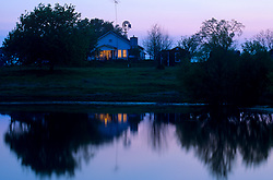 farm house on a pond at dusk
